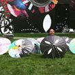 artist and parasols in front of mural